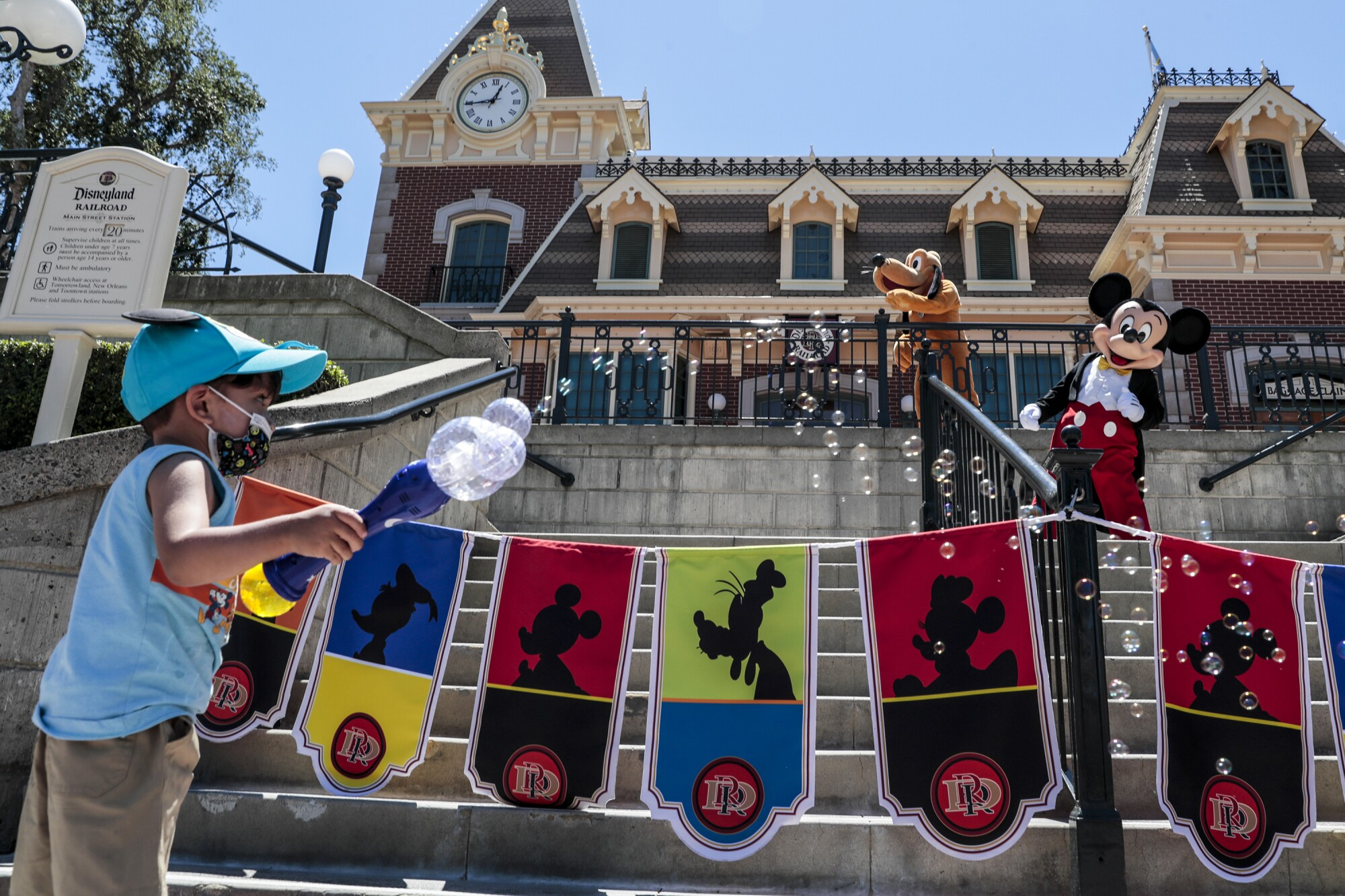 A masked employee greets a Disneyland visitor wearing Minnie Mouse-themed gear