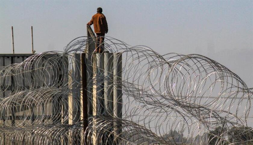 Una persona burla las alambradas de acero en Tijuana (México). La ilusión en México de cientos de integrantes de la caravana migrante de centroamericanos, que aguardan con paciencia la llegada del resto de sus compañeros, unos 3.000 que se trasladan desde Mexicali, ha encontrado un espacio en los puentes de la fronteriza ciudad de Tijuana. EFE