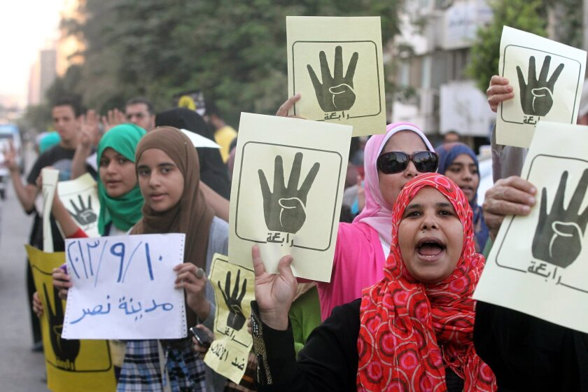 During a protest in Cairo, supporters of ousted President Mohamed Morsi hold posters with a hand in a sign of the number four, a reference to a mosque where troops cracked down on demonstrators last month.