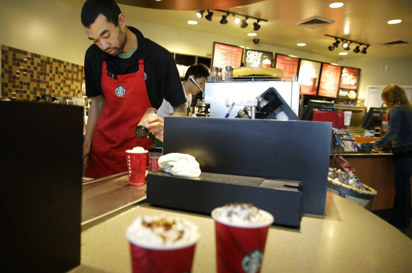 Jay Rapp prepares a chestnut praline latte at a Starbucks store in Seattle. On Monday, Starbucks said it will offer its employees four years of tuition-free online education through Arizona State University.