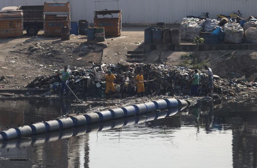 En esta imagen del 28 de julio de 2015, trabajadores retiran la basura recolectada de barreras flotantes en un canal en la favela Mare, en Río de Janeiro, Brasil. El problema histórico de las aguas residuales de Río se incrementó durante la última década debido al crecimiento demográfico, y a que gran parte de los 12 millones de residentes del área metropolitana se han establecido en las grandes favelas que rodean la bahía. Los desperdicios fluyen a más de 50 arroyos que desembocan en lo que alguna vez fueron aguas cristalinas de Bahía Guanabara.