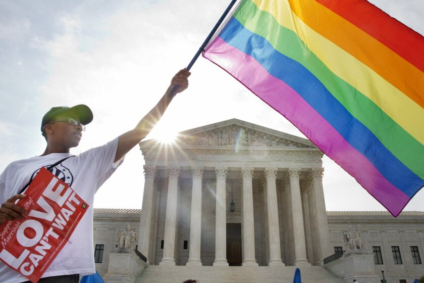 A supporter of same-sex marriage waves a flag outside the U.S. Supreme Court.