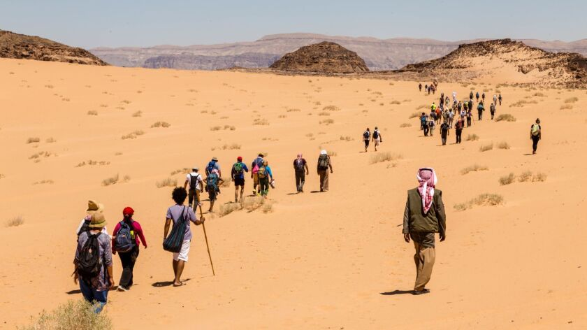 ONE TIME USE - South Sinai, Egypt - May 12, 2018: Hikers led by Bedouins through the sand dunes sect
