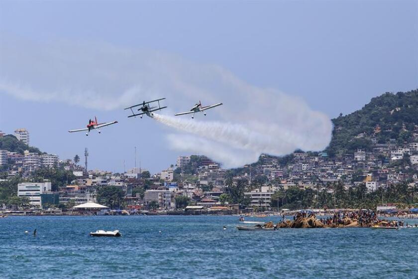 Turistas observan avionetas que realizan acrobacias hoy, sábado 11 de agosto de 2018, en el balneario de Acapulco, Guerrero (México). EFE