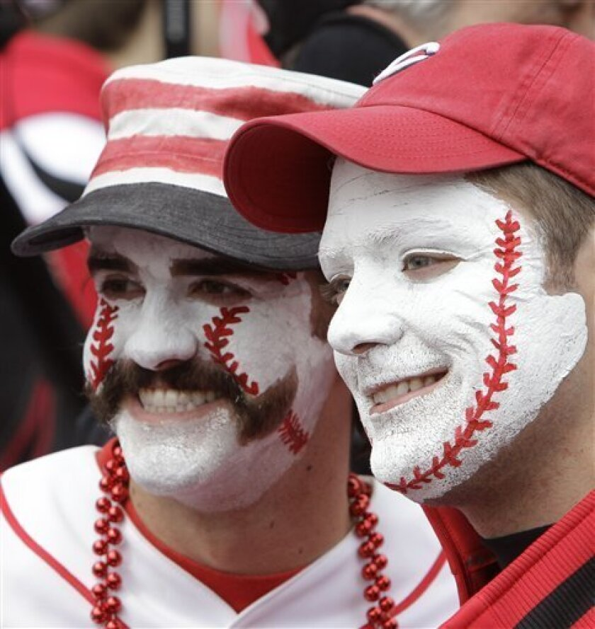 Cincinnati Reds fans Kyle Hackenberg, left, and Eric Myers pose for pictures for another fan during batting practice before the Reds opening day baseball game against the Milwaukee Brewers, Thursday, March 31, 2011, in Cincinnati. (AP Photo/Al Behrman)