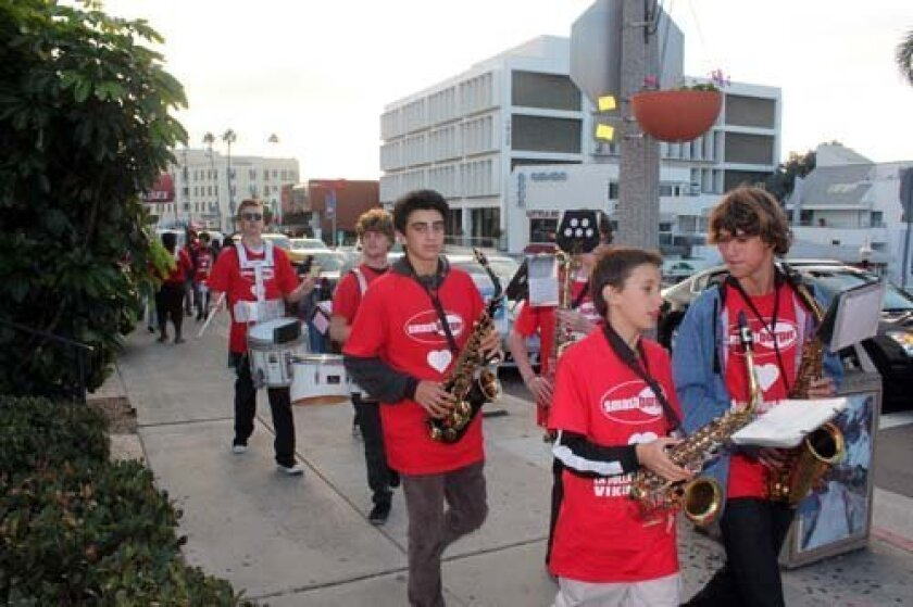 Band members walk along Prospect on Tuesday evening. Photo: Dave Schwab
