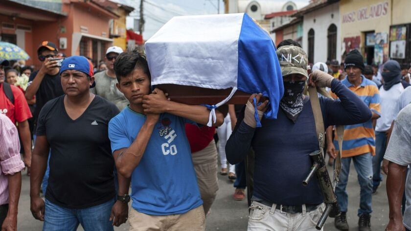 Friends and family carry the coffin with the body of Jose Esteban Sevilla Medina, who died after he