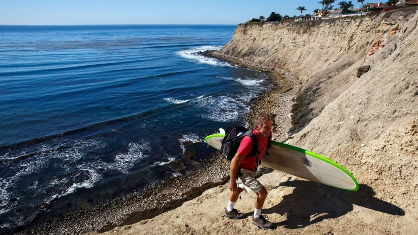 A man who declined to give his name carries a surfboard up a trail as city contractors demolish a patio built by local surfers.