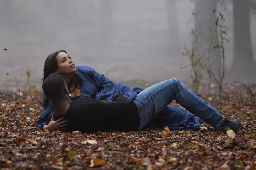Michael B. Jordan and Lauren London lie on leaf-covered ground amid trees and fog.