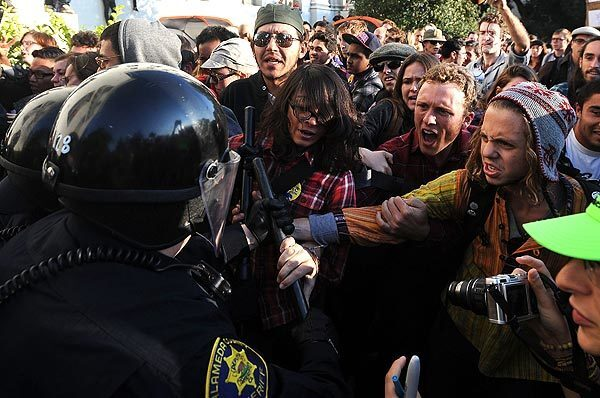 Riot police hold back Occupy Berkeley protesters as tents are dismantled on Wednesday in Sproul Plaza at UC Berkeley.