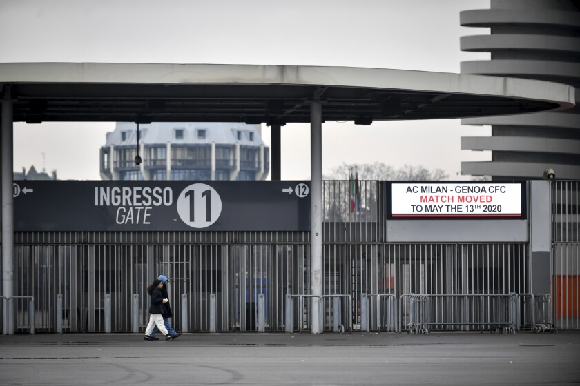 People walk outside San Siro stadium where a notice advising that the Serie A soccer match between AC Milan and Genoa is postponed to May 13, 2020, in Milan, Italy.