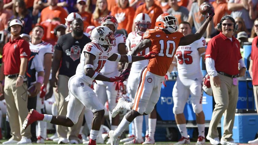 Clemson's Derion Kendrick (10) tries a one-handed catch while defended by North Carolina State'sChri