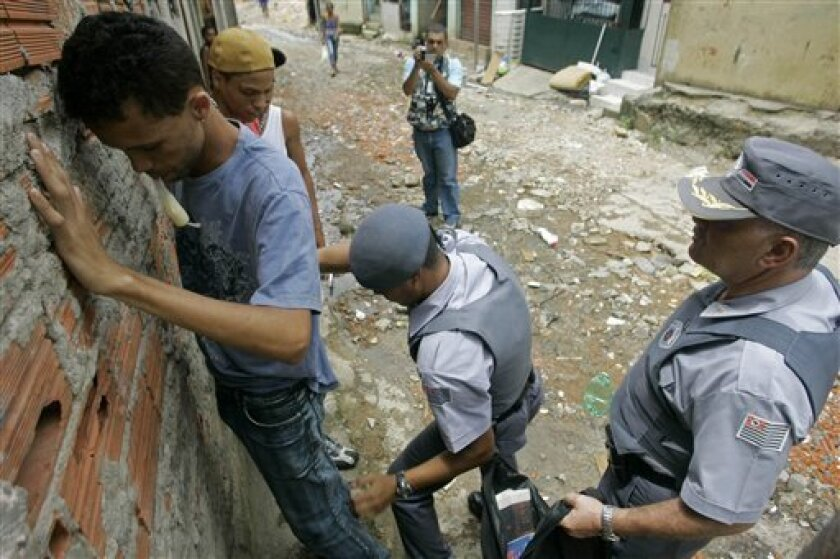Police search residents as they patrol Paraisopolis slum in Sao Paulo, Tuesday, Feb. 3, 2009. Hundreds of riot police occupied one of Sao Paulo's biggest slums Tuesday following a night of shootouts and car burnings that saw three police officers shot in street combat with bands of young men. (AP Photo/Nelson Antoine)