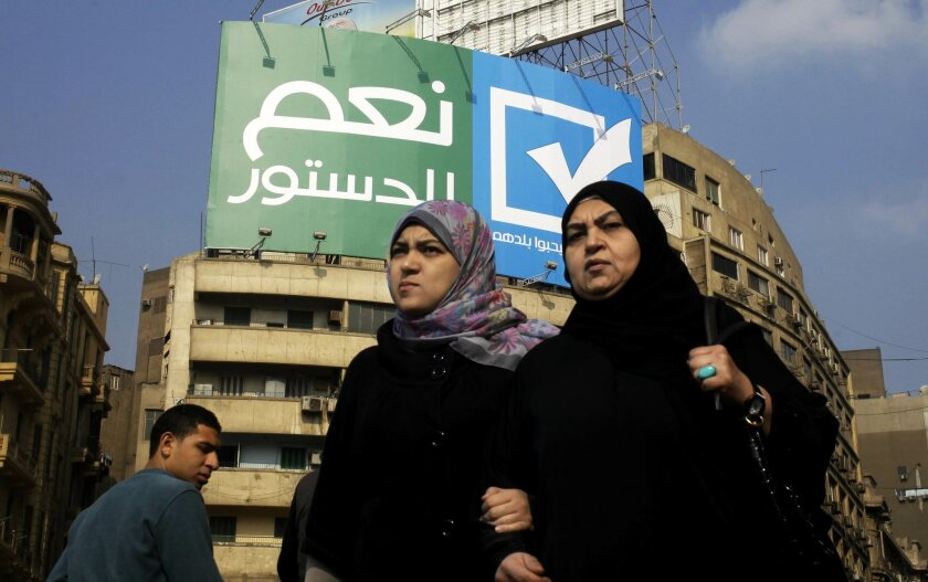 """FILE - In this Saturday, Jan. 11, 2014 file photo, Egyptians walk under a billboard with Arabic that reads, """"yes to the constitution, Egyptians love their country,"""" in Tahrir Square, Cairo, Egypt. With a presidential run by Egypt's powerful military chief seeming more likely by the day, this week's two-day constitution referendum, to be held amid a massive security force deployment, is widely seen as a vote of confidence in the regime he installed last summer. (AP Photo/Amr Nabil, File)"""
