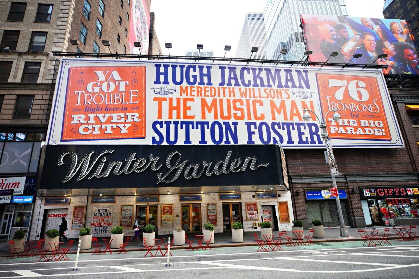 """The exterior of Winter Garden theater has a large banner advertising """"The Music Man,"""" Hugh Jackman and Sutton Foster."""