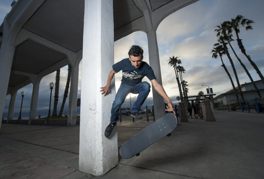 Kilian Martin performs a wall plant off of the Oceanside Pier last week. The pier and its adjacent amphitheater are among his favorite practice spots.