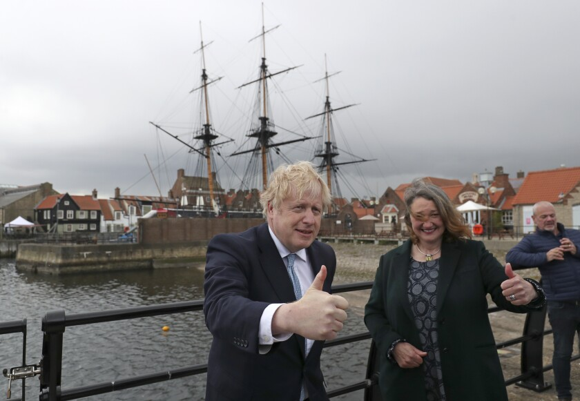 British Prime Minister Boris Johnson poses for photographers with Jill Mortimer, the winning Conservative Party candidate of the Hartlepool by-election, at Hartlepool Marina, in Hartlepool, north east England, Friday, May 7, 2021. Britain's governing Conservative Party made further inroads in the north of England on Friday, winning a by-election in the post-industrial town of Hartlepool for a parliamentary seat that the main opposition Labour Party had held since its creation in 1974. (AP Photo/Scott Heppell)