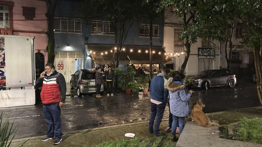 La gente se reúne en una calle después de un fuerte sismo que se sintió en la colonia Roma en Ciudad de México