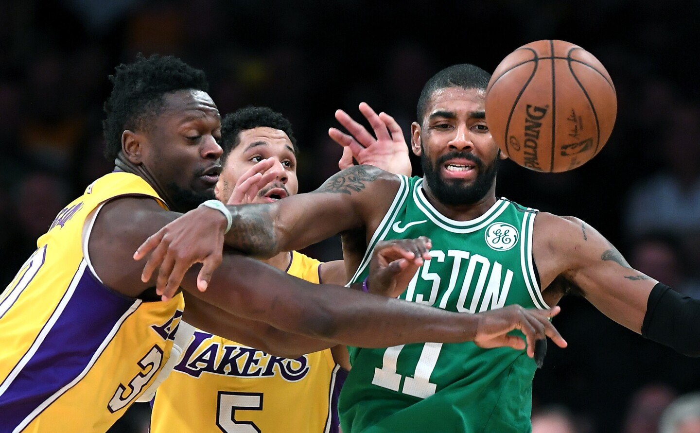 Lakers forward Julius Randle knocks the ball away form Celtics guard Kyrie Irving during the fourth quarter of a game Tuesday at Staples Center.