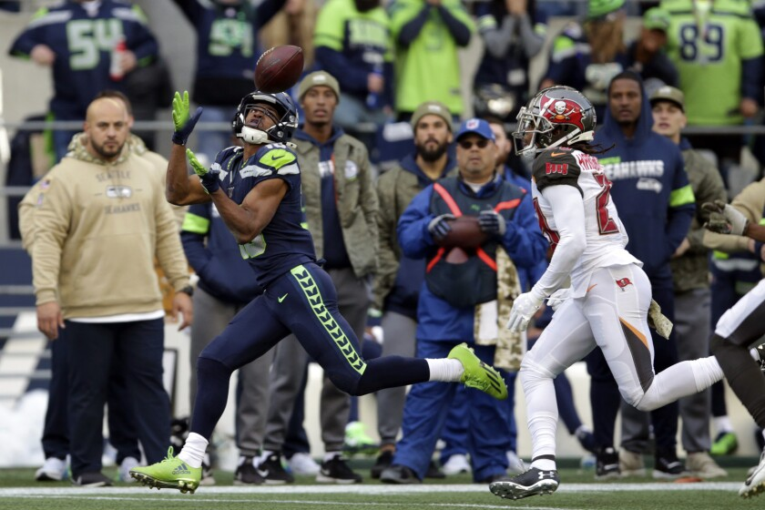 Seattle Seahawks wide receiver Tyler Lockett, left, catches a pass ahead of Tampa Bay Buccaneers cornerback Vernon III Hargreaves, right, during the second half of an NFL football game, Sunday, Nov. 3, 2019, in Seattle. (AP Photo/Scott Eklund)