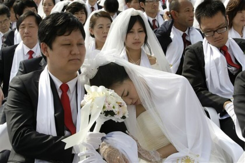 An unidentified bride takes a nap during a mass wedding ceremony in Asan, South Korea, Sunday, Oct. 10, 2010. Some 7,200 South Korean and foreign couples exchanged or reaffirmed marriage vows in the Unification Church's second mass wedding this year.(AP Photo/Ahn Young-joon)