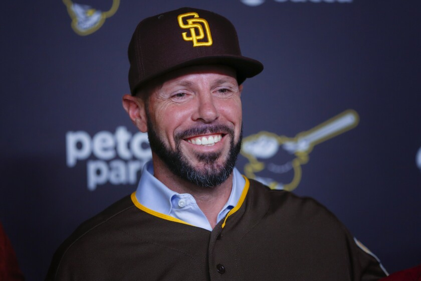 Padres manager Jayce Tingler poses for pictures last week while wearing the team's new brown and gold cap.
