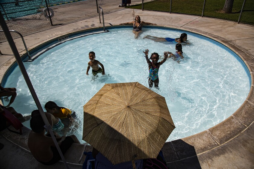 Adults and children cool off in the pool as the temperature tops 100 degrees Aug. 5 at Shamel Park Pool in Riverside.
