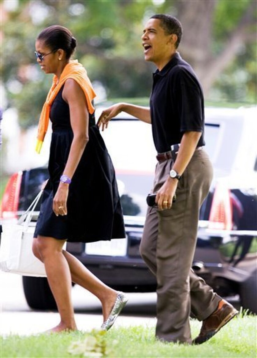 President Barack Obama with first lady Michelle Obama, greets a crowd across the street from the landing site at Fort Lesley J. McNair, Saturday, July 4, 2009, in Washington. (AP Photo/Manuel Balce Ceneta)