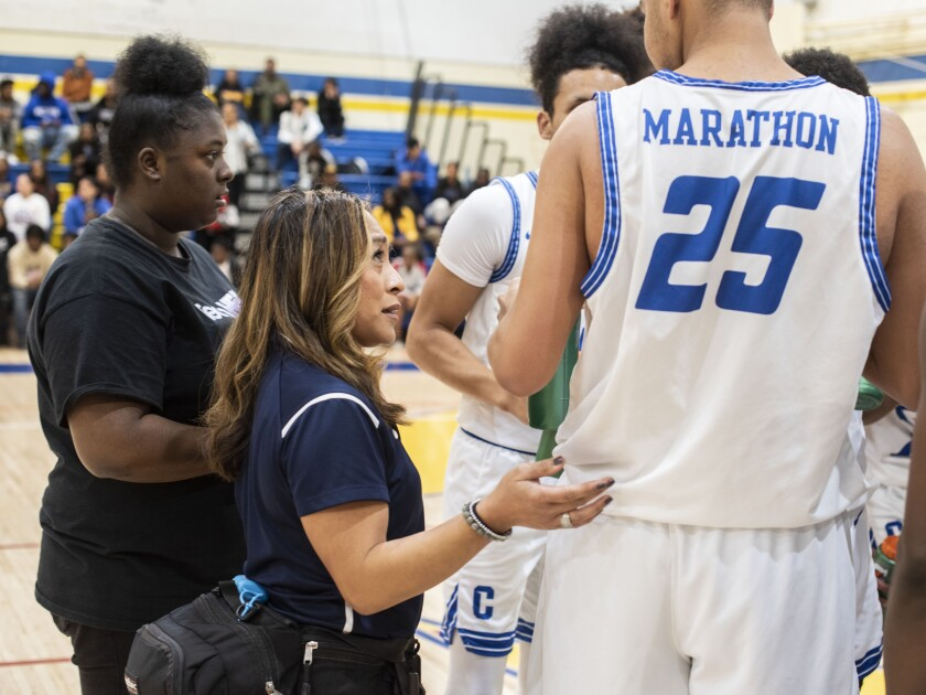 Athletic trainer Ellen Kelly checks in with one of the Crenshaw basketball players during a game Jan. 24, 2020.