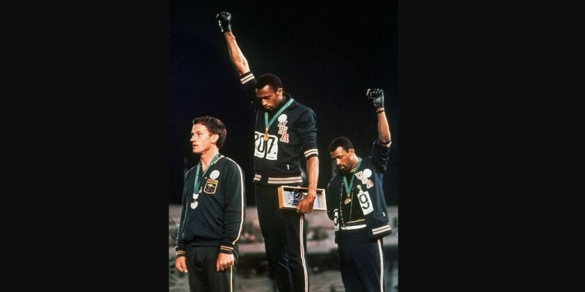 """In this Oct. 16, 1968, extending gloved hands skyward in protest, U.S. athletes Tommie Smith, center, and John Carlos stare downward during the playing of """"The Star-Spangled Banner"""" at the Summer Olympic Games in Mexico City. Australian silver medalist Peter Norman is at left."""