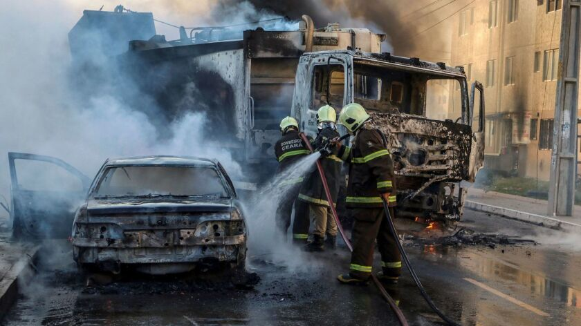 Firefighters extinguish burning vehicles Jan. 3 during a wave of violence in Fortaleza, capital of Brazil's northeastern Ceara state.