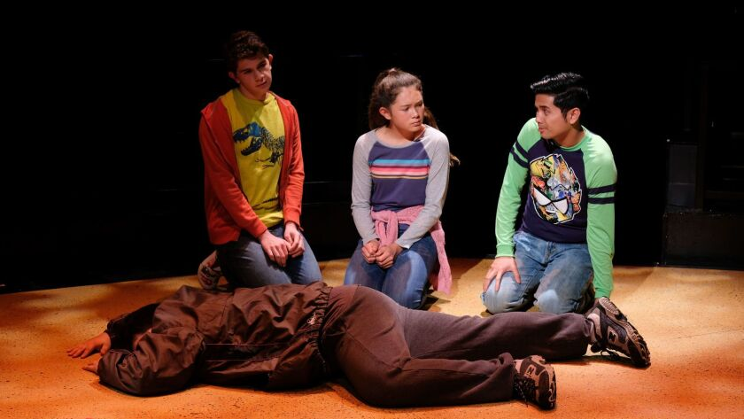 """Dylan Nalbandian, left, Olivia Weise and Wilfred Paloma observe a prone man, played by Victor Reveles, in Tan'yeasia Brewster's """"Some-Body,"""" one of four plays getting a full production at Playwrights Project's 33rd Plays By Young Writers Festival at The Old Globe."""