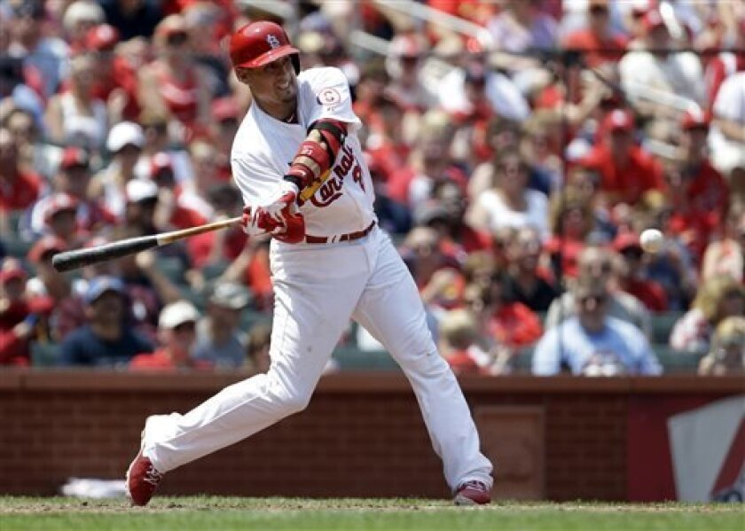 St. Louis Cardinals' Allen Craig swings on a sacrifice fly to score Matt Carpenter during the third inning of a baseball game against the Miami Marlins on Sunday, July 7, 2013, in St. Louis. (AP Photo/Jeff Roberson)