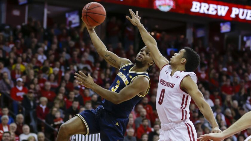 Michigan's Zavier Simpson (3) shoots against Wisconsin's D'Mitrik Trice (0) during the first half.