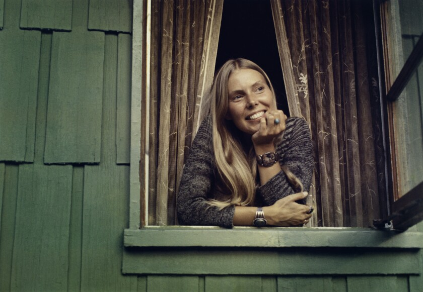 Joni Mitchell looks out a window, smiling