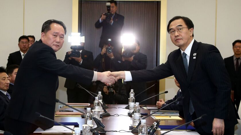 South Korean Unification Minister Cho Myoung-gyon, right, shakes hands with the head of North Korean