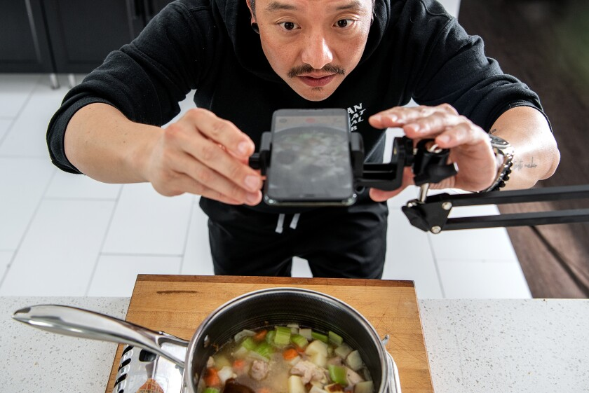 Chris Oh films the making of his cheesy Japanese curry chicken pot pie at his home in Los Angeles.