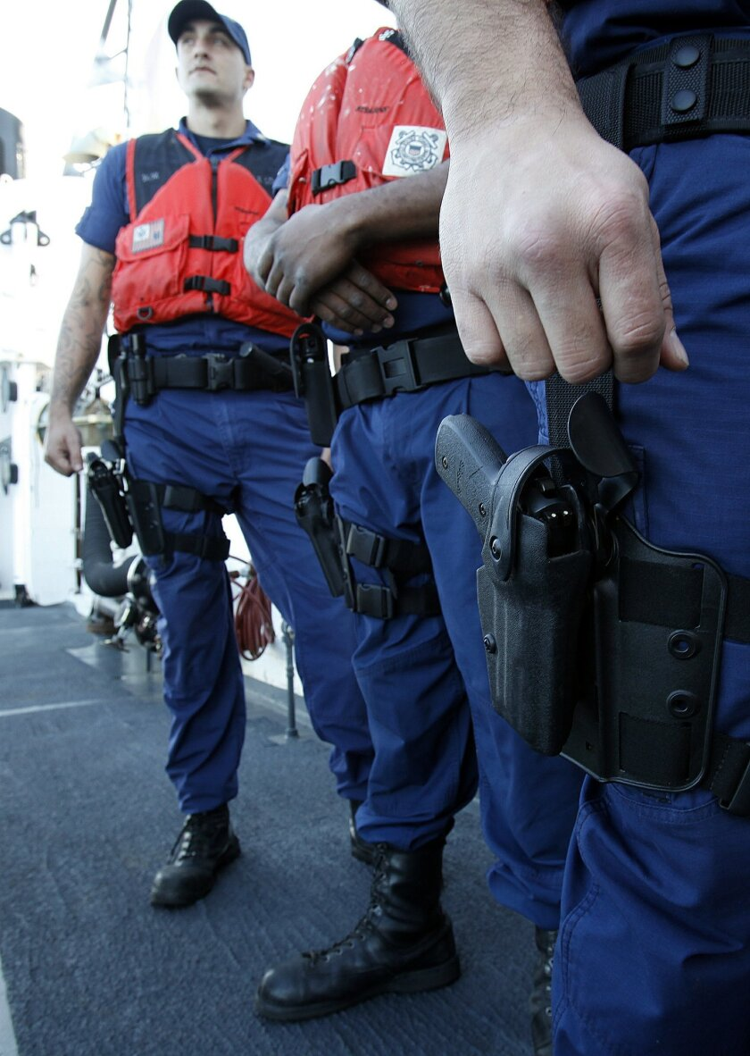 With .40 caliber Sig-Sauer's strapped to their thighs, the law enforcement boarding team prepped during a drill aboard the Boutwell.