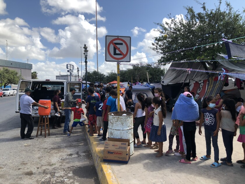 Migrants line up to receive food and water distributed by a Mexican minister at Plaza Las Americas migrant camp in Reynosa.