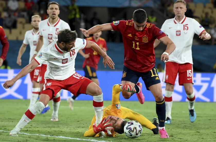 El defensor polaco Bartosz Bereszynski, el portero polaco Wojciech Szczesny y el español Ferrán Torres disputan el balón durante el partido entre España y Polonia por el Grupo E de la Eurocopa en Sevilla, España, sábado 19 de junio de 2021. (Lluis Gene/Pool via AP)