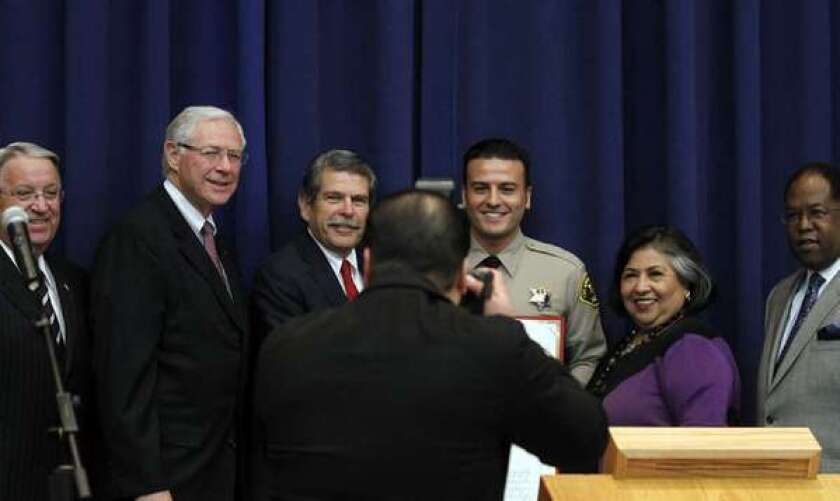 The five Los Angeles County supervisors pose with a sheriff's deputy.