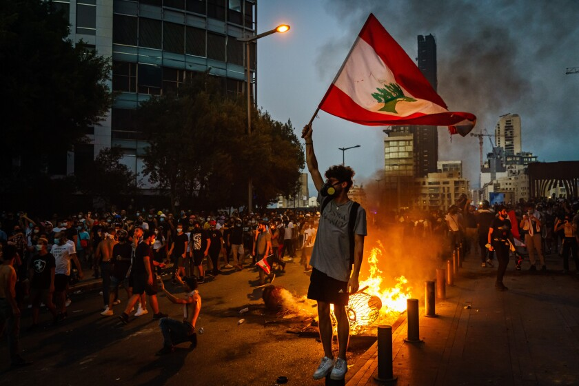 A protester holds up a Lebanese flag in front of a small fire in the street