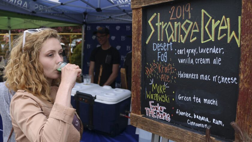 In this photo taken May 18, 2019, a woman tastes a green tea mocha beer at the Strange Brew Festival