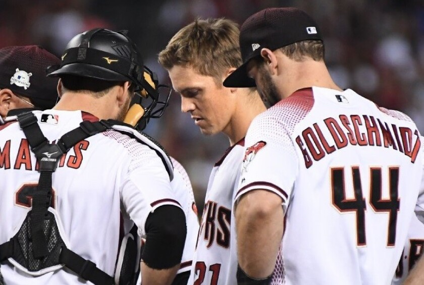 Diamondbacks pitcher Zach Greinke, center, looks down as he comes out of Game 3 of the National League division series.