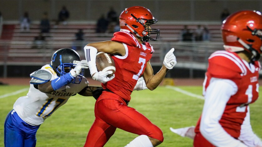 Lawndale's Makell Esteen tries to outrun the tackle attempt by a Crenshaw defensive back after making a catch during a game on Sept. 14, 2018.