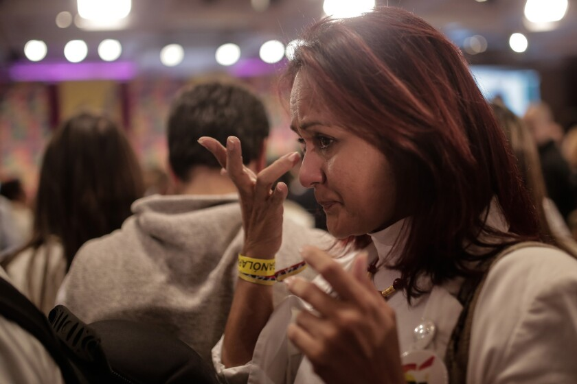 A Colombian woman reacts Sunday as results come in showing voters narrowly rejecting a proposed peace accord between the government and FARC rebels.