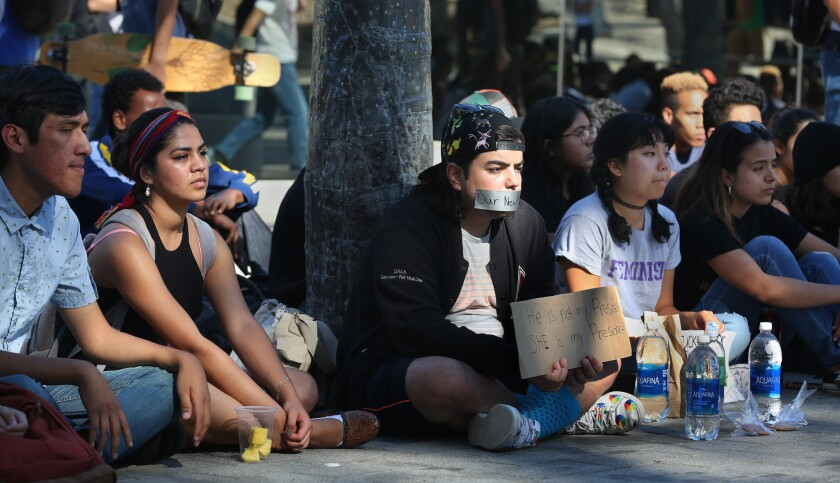 """William P. Yeromian sits with tape over his mouth reading """"Our New America"""" and a sign reading """"He's not my president, She's my president,"""" with other students at UCSD staging a protest Wednesday after the results of the presidential election."""