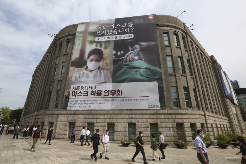 """People wearing face masks to help protect against the spread of the coronavirus walk under a banner informing mandatory mask wearing in front of Seoul City Hall in Seoul, South Korea, Thursday, Sept. 17, 2020. The banner reads: """" Which mask would you wear?"""" (AP Photo/Ahn Young-joon)"""