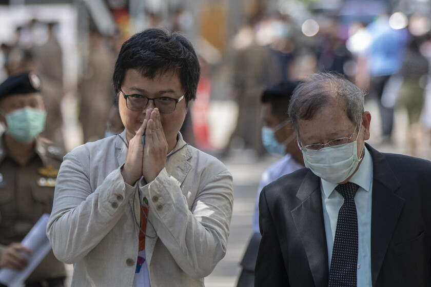 Pro-democracy activist and human rights lawyer Arnon Nampha, left, greets as he arrives at criminal courthouse for hearing to determine whether he has violated his bail conditions in Bangkok, Thailand, Thursday, Sept. 3, 2020. Growing pro-democracy protests have emerged as the most serious threat to the government led by a former army general accused of incompetence and corruption by protesters. (AP Photo/Gemunu Amarasinghe)