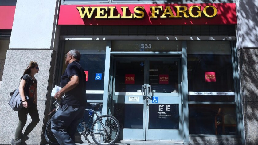 Pedestrians walk past a branch of Wells Fargo bank in downtown Los Angeles on Oct. 3.